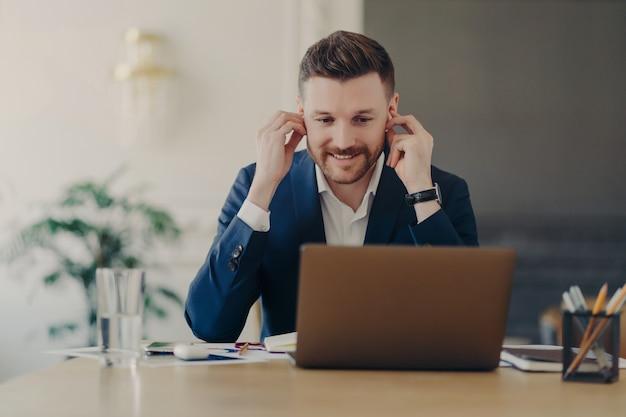 Gelukkige zakenman of mannelijke werkgever die draadloze oortelefoons gebruikt en online vergadert, een formeel blauw pak draagt terwijl hij voor een laptop aan het bureau zit met notitieblok, potloden en glas water