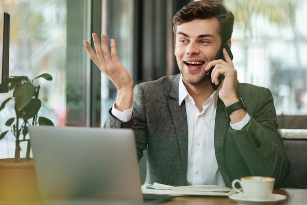Gelukkige zakenmanzitting door de lijst in koffie met laptop computer en het spreken door smartphone terwijl weg het kijken