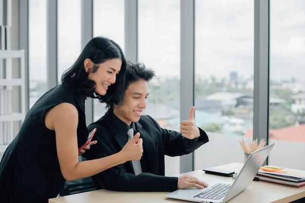 Gelukkige zakenmensen met duimen omhoog op videogesprek met laptop op kantoor