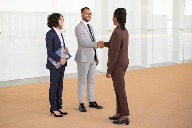 Gelukkige zakenpartners die elkaar begroeten