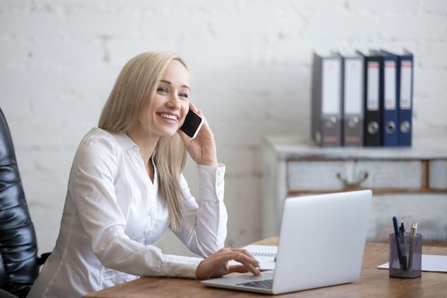 Gelukkige zakenvrouw die in haar kantoor werkt