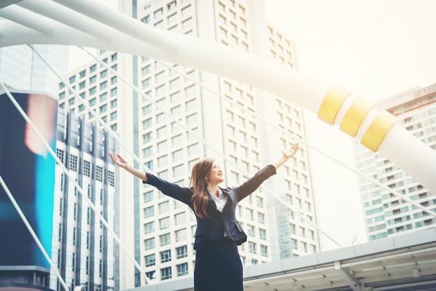 Gelukkige zakenvrouw excults pompen vuisten extatische feest succes buiten.