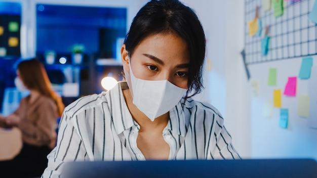Gelukkige zakenvrouw in azië die een medisch gezichtsmasker draagt voor sociale afstand in een nieuwe normale situatie voor viruspreventie tijdens het gebruik van een laptop op het werk in de kantoornacht.