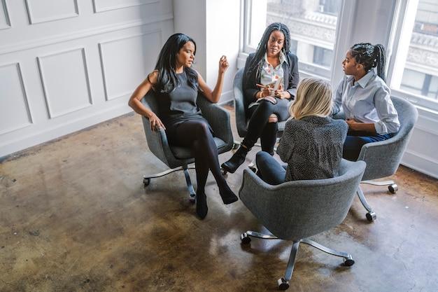Gelukkige zakenvrouwen die een vergadering hebben op kantoor