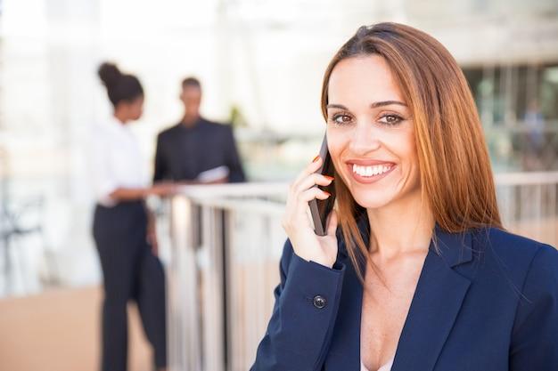 Gelukkige zekere onderneemster die op mobiele telefoon spreekt