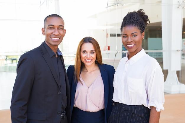 Gelukkige zelfverzekerde jonge interracial teamleden omarmen