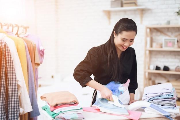 Gelukkige zoete thaise meid huishoudster strijken kleding.