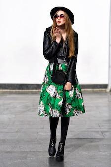 Gelukkige zonnige lentetijd van mooie jonge vrouw met lang donkerbruin haar in hoed, lange groene rok, op hielen die op straat lopen. modieus model, positieve emoties uitdrukken voor camera, glimlachen, vreugde