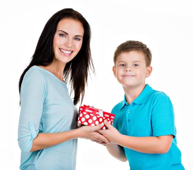 Gelukkige zoon die een gift geeft aan zijn moeder die op wit wordt geïsoleerd