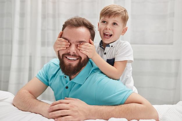 Gelukkige zoon die verrassing maakt aan vader Premium Foto