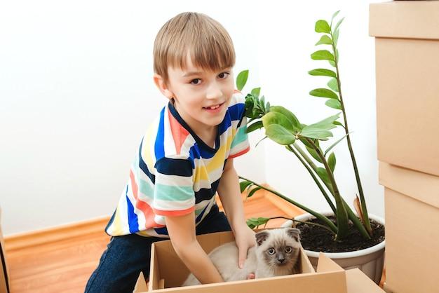 Gelukkige zoon en een kat die samen plezier hebben bij het verplaatsen van de dag in het nieuwe huis.
