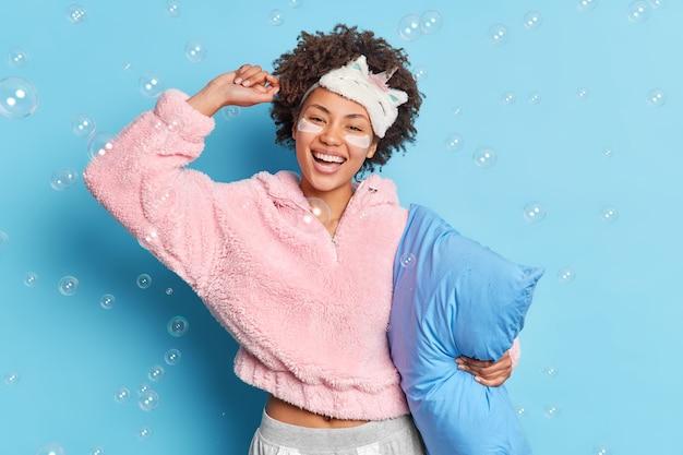 Gelukkige zorgeloze jonge vrouw danst met opgeheven armen heeft plezier voordat ze naar bed gaat houdt kussen draagt pyjama geïsoleerd over blauwe muur