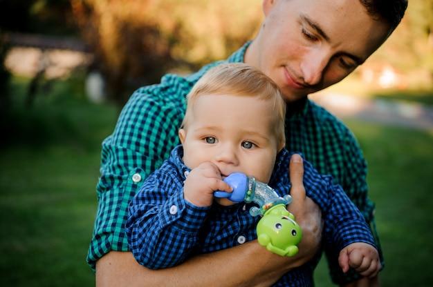 Gelukkige zorgzame vader die op handen een babyjongen met een fopspeen houdt