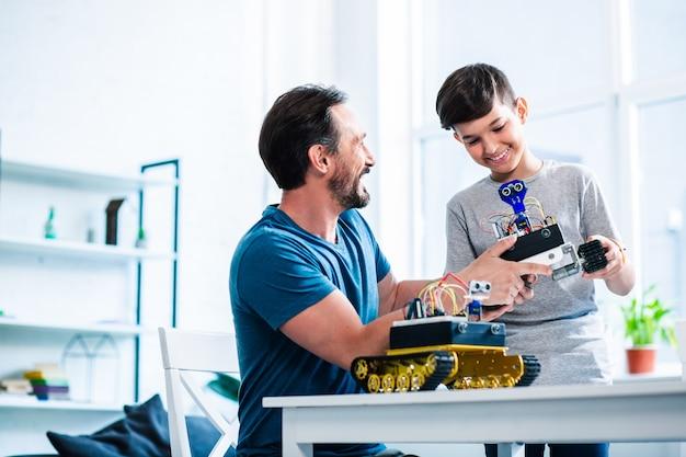 Gelukkige zorgzame vader en zijn zoon houden robotapparaten vast terwijl ze samen aan een technisch project werken