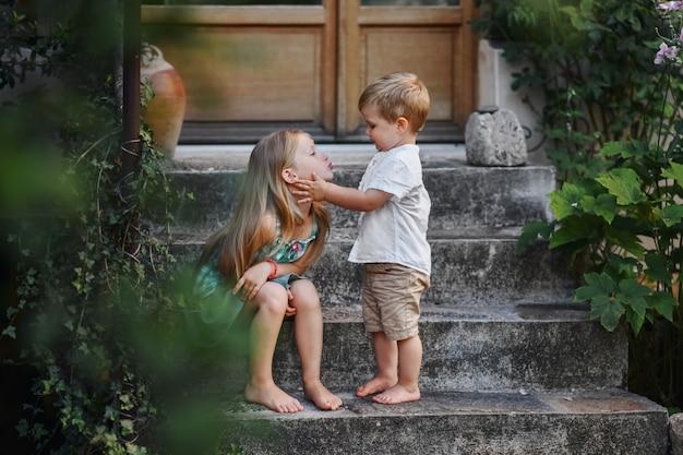 Gelukkige zus en broer samen in de zomertuin
