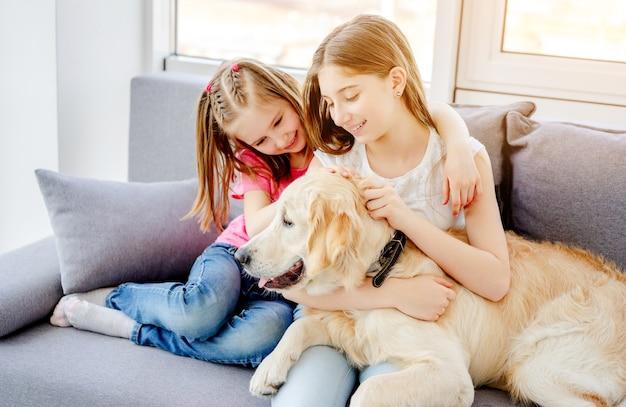 Gelukkige zussen die schattige hond knuffelen die thuis op de bank zit