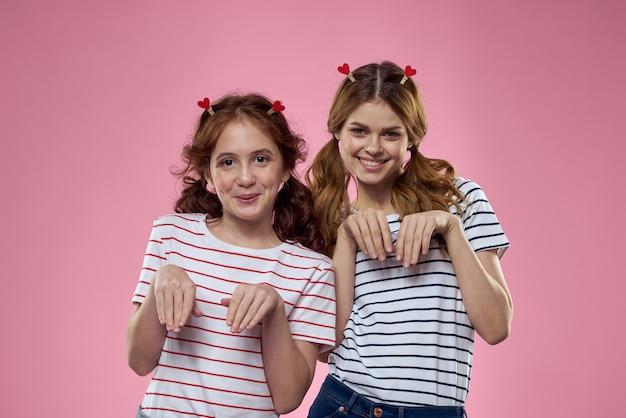 Gelukkige zussen vermaken zich op een roze muur en hartvormige wasknijpers op hun hoofd.