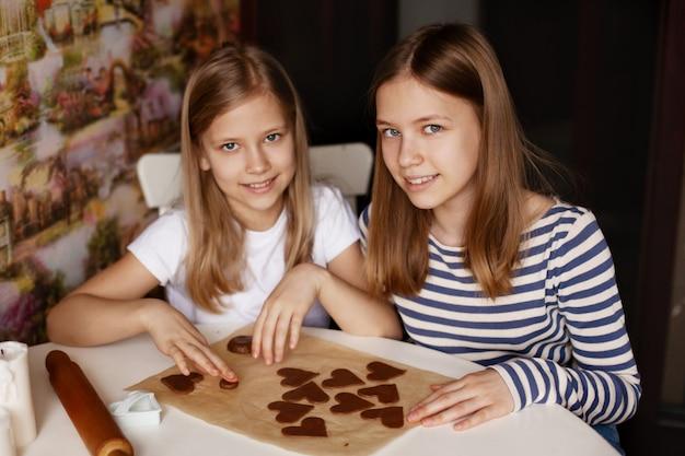 Gelukkige zusters in de huiskeuken aan de tafel haken hartvormige koekjes uit het deeg