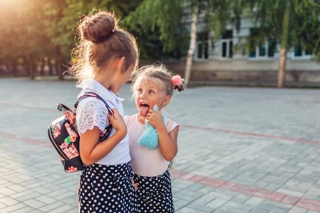 Gelukkige zustersmeisjes die rugzakken dragen en pret hebben.