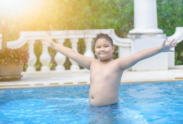 Gelukkige zwaarlijvige dikke jongen in zwembad,