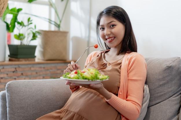 Gelukkige zwangere aziatische vrouw die en natuurlijk plantaardig salade gezond voedsel zitten eten en op bank zitten