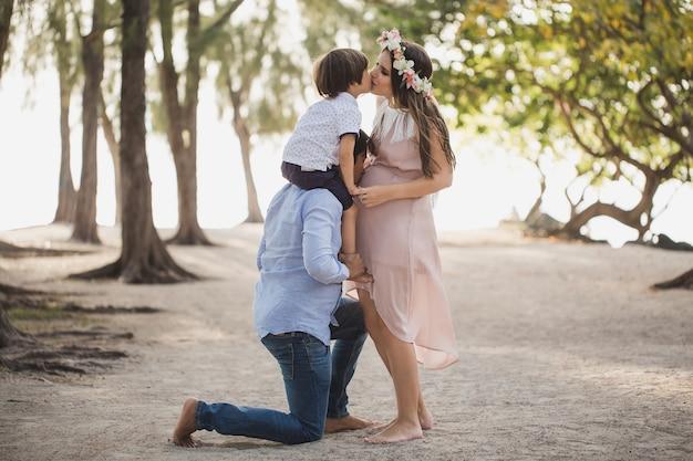 Gelukkige zwangere familie die plezier heeft in de natuur. zoon op de schouders van je vader. papa kust zijn zwangere vrouw in de maag.