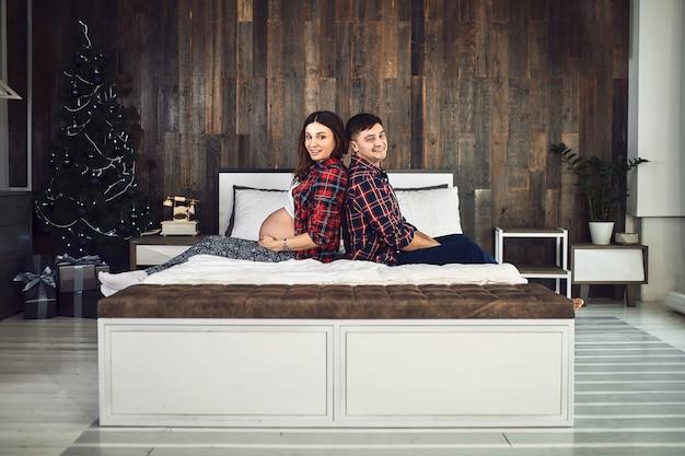 Gelukkige zwangere familie ligt thuis op het bed. hij plant een gezinsleven in afwachting van de baby. gezinsgeluk, de geboorte van een kind.