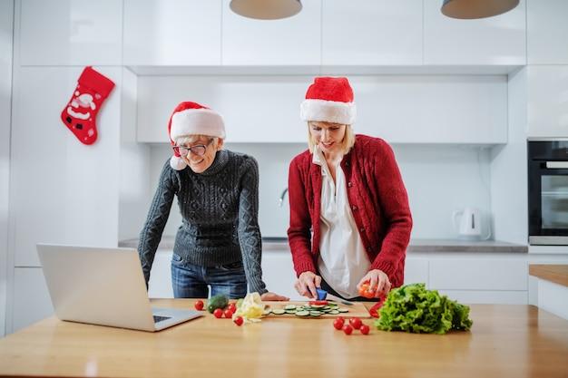 Gelukkige zwangere kaukasische vrouwen hakkende groenten voor oudejaarsavondmaaltijd terwijl haar moeder na recept op laptop. beiden met kerstmutsen op het hoofd. familiewaarden concept.