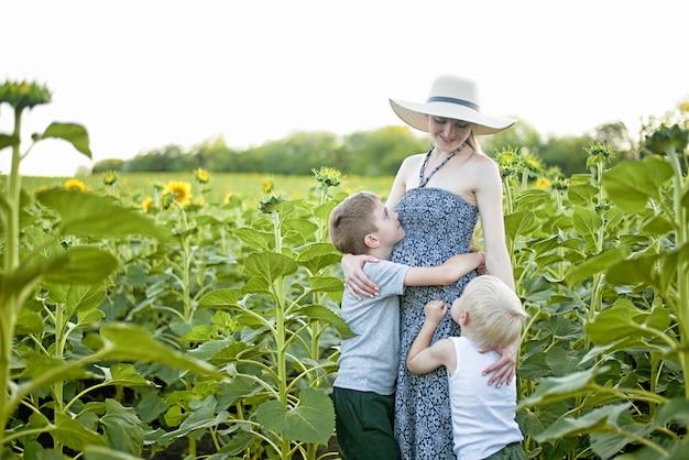 Gelukkige zwangere moeder die twee kleine zonen op een gebied van bloeiende zonnebloemen koestert