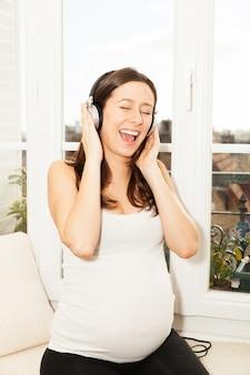 Gelukkige zwangere vrouw die en aan muziek zingt luistert