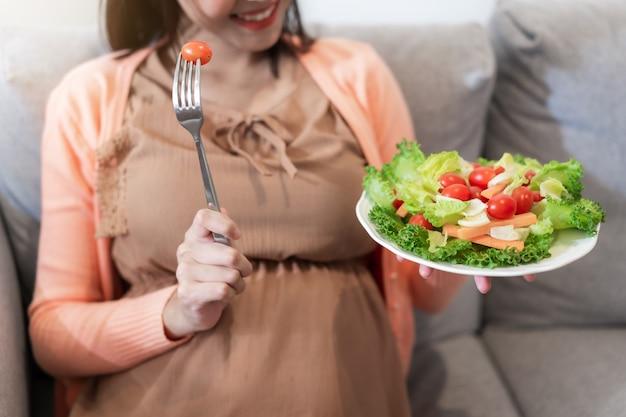 Gelukkige zwangere vrouw die en natuurlijke plantaardige salade zitten eten
