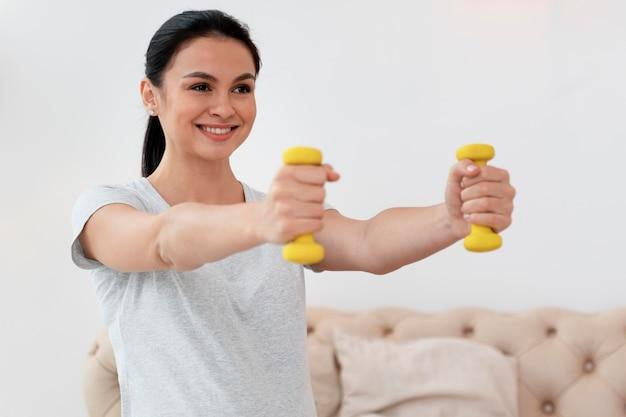 Gelukkige zwangere vrouw die gele gewichten gebruikt