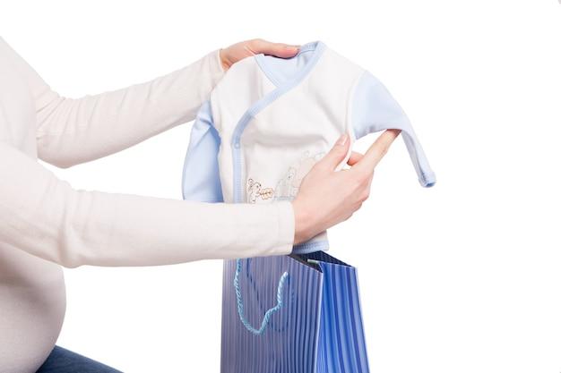 Gelukkige zwangere vrouw die kleren van kind boven pakket over wit houdt