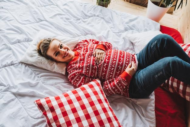 Gelukkige zwangere vrouw die op een bed en het glimlachen ligt
