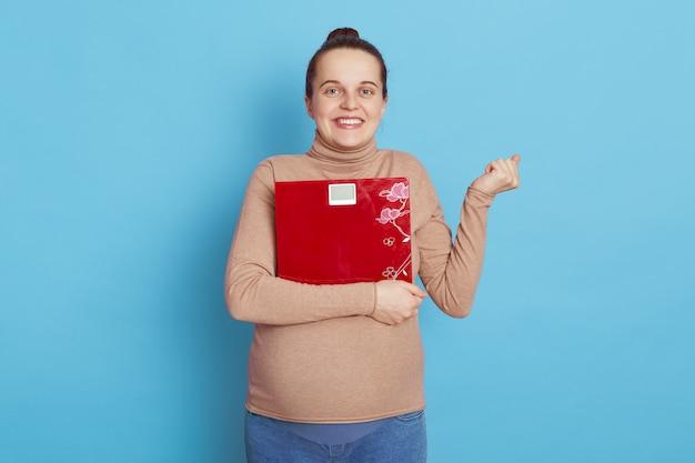 Gelukkige zwangere vrouw die vloerweegschalen omhelst en direct camera bekijkt, balde vuist met opwinding die over blauwe muur wordt geïsoleerd.