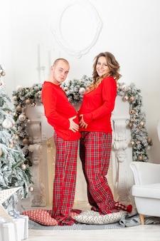 Gelukkige zwangere vrouw en man hebben plezier in het kerstinterieur
