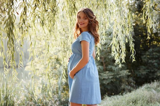 Gelukkige zwangere vrouw in het park