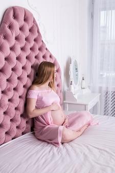 Gelukkige zwangerschapszitting op bed thuis in slaapkamer