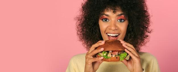 Gelukkige zwarte die met golvende haren smakelijke cheeseburger op roze eet.