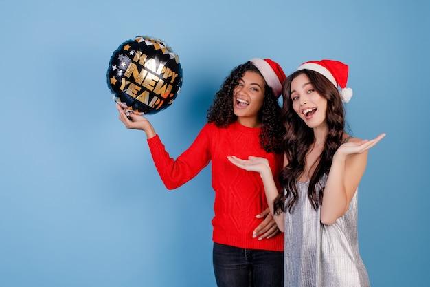 Gelukkige zwarte en kaukasische dame met gelukkige nieuwe jaarballon en santahoeden