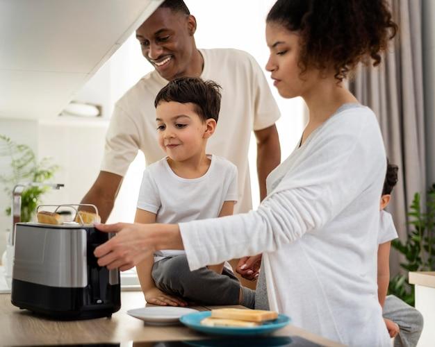 Gelukkige zwarte familie die ontbijtvoedsel voorbereidt