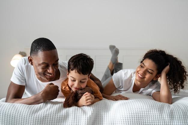 Gelukkige zwarte familie die terwijl tot in bed glimlacht
