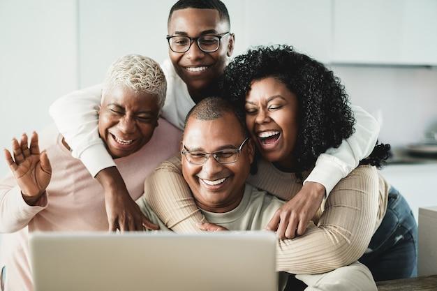 Gelukkige zwarte familie die videogesprek thuis doet - belangrijkste nadruk op vadergezicht
