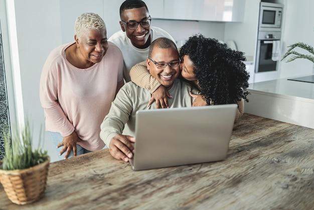 Gelukkige zwarte familie die videogesprek thuis doet - belangrijkste nadruk op zoongezicht