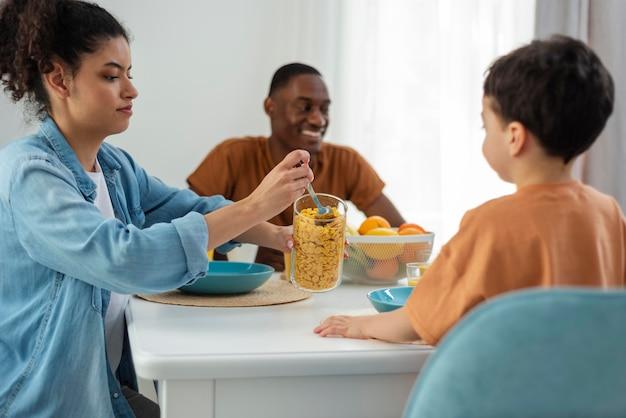 Gelukkige zwarte familie met moeder die jong geitje dient