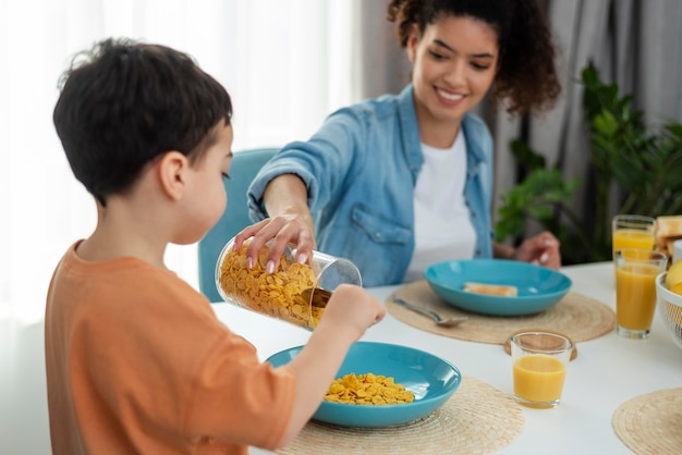 Gelukkige zwarte familie met moeder die jong geitje met cornflakes dient