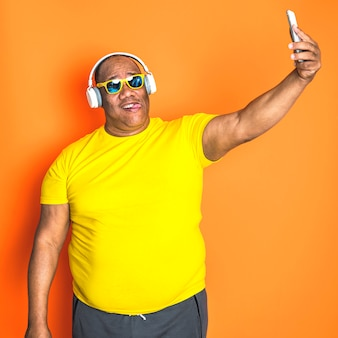Gelukkige zwarte hogere mens die zijn slimme telefoon met behulp van. concept van technologie en communicatie bij ouderen