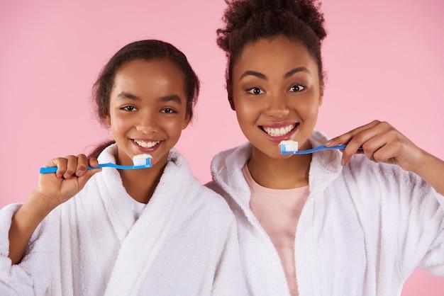 Gelukkige zwarte moeder en dochter in peignoir