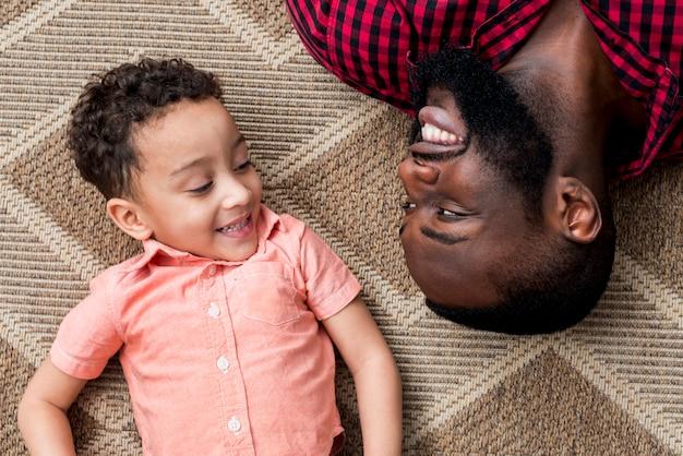 Gelukkige zwarte vader en zoon die op vloer liggen