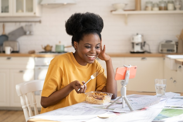 Gelukkige zwarte vrouw praat met een vriend via videogesprek tijdens het diner of pauze van het werk bij covid-epidemie